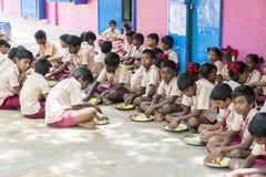 新闻纪录片的社论图象 未认出的孩子吃午餐在军用餐具 免版税图库摄影