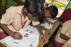 新闻纪录片的社论图象 未认出的小学生在教室学习在政府公立学校 库存照片