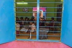 新闻纪录片的社论图象 未认出的小学生在教室学习在政府公立学校 库存图片