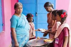 新闻纪录片的社论图象 未认出womaen午餐的服务孩子在室外军用餐具 图库摄影