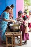 新闻纪录片的社论图象 未认出womaen午餐的服务孩子在室外军用餐具 库存照片