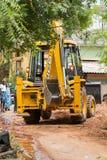 新闻纪录片的社论图象 黄色推土机,有准备好的桶的拖拉机,与人观看一起使用 免版税库存照片