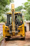 新闻纪录片的社论图象 黄色推土机,有准备好的桶的拖拉机,与人观看一起使用 库存照片