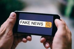 新闻SEO概念:关闭假新闻被显示在智能手机显示的查寻酒吧 免版税库存照片