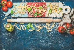 新面团casarecce,蕃茄,蓬蒿,在五颜六色的委员会的橄榄油 免版税库存图片