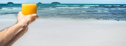 新饮料在人在异乎寻常的海滩的背景的` s手上, 免版税库存照片