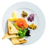 新鲜三文鱼鞑靼与在a的油煎方型小面包片、沙拉和柠檬切片 库存图片