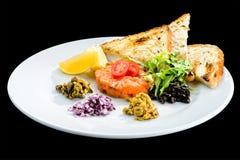 新鲜三文鱼鞑靼与在a的油煎方型小面包片、沙拉和柠檬切片 库存照片