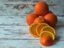 新鲜和切的桔子在木背景的形状安排了,与文本的空间在书桌上 免版税库存图片