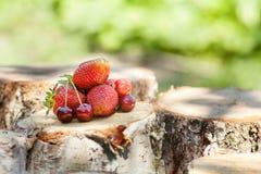 新鲜和开胃草莓用在木日志的红色樱桃 免版税库存图片