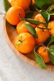 新鲜和水多的蜜桔板材与叶子的在一块白色石头 免版税库存照片