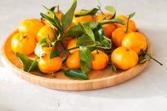 新鲜和水多的蜜桔板材与叶子的在一块白色石头 免版税图库摄影
