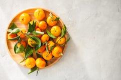 新鲜和水多的蜜桔板材与叶子的在一块白色石头 免版税库存图片