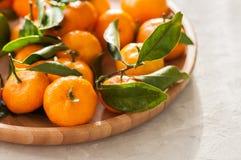 新鲜和水多的蜜桔板材与叶子的在一块白色石头 库存照片