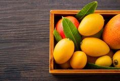 新鲜和美丽的芒果果子在黑暗的木背景,拷贝spacetext空间的一个木箱设置了 免版税库存照片