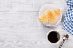 新鲜咖啡的新月形面包 免版税库存图片