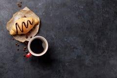 新鲜咖啡的新月形面包 库存照片