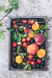 新鲜水果和莓果在木箱在石桌 免版税库存照片