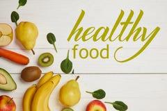 新鲜水果和菠菜顶视图在白色木背景离开与拷贝空间,健康食物题字 免版税库存图片
