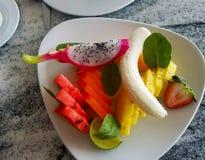 新鲜水果在一张大理石桌上的一个白色盘服务与dragonfruit 免版税库存图片