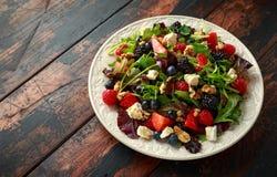 新鲜水果沙拉用蓝莓、草莓莓、核桃、希腊白软干酪和绿色菜 r 图库摄影