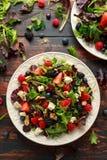 新鲜水果沙拉用蓝莓、草莓莓、核桃、希腊白软干酪和绿色菜 r 免版税库存图片