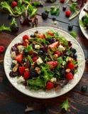 新鲜水果沙拉用蓝莓、草莓莓、核桃、希腊白软干酪和绿色菜 r 免版税图库摄影