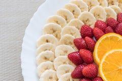 新鲜水果的五颜六色的混合在一块白色板材的 免版税库存照片