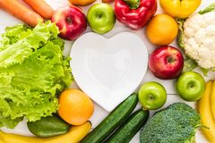 新鲜水果顶视图与菜的和倒空在木的心形的板材 免版税库存照片