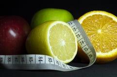 新鲜水果:苹果、切的桔子和柠檬与测量的磁带 黑色背景 免版税库存图片