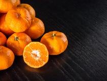 新鲜的一半桔子和整个桔子与拷贝空间在黑色 免版税图库摄影