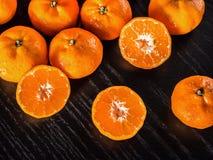 新鲜的一半桔子和整个桔子与拷贝空间在黑色 免版税库存照片