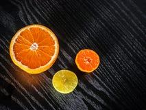 新鲜的一半桔子和石灰与拷贝空间在黑桌上 免版税图库摄影