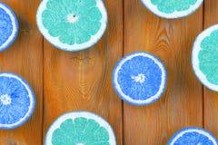新鲜的一半裁减葡萄柚和桔子在蓝色木背景,关闭看法 图库摄影