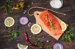 新鲜的三文鱼内圆角的可口部分用芳香草本、香料和菜-健康食物,饮食或烹调概念 免版税图库摄影