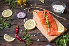 新鲜的三文鱼内圆角的可口部分用芳香草本、香料和菜-健康食物,饮食或烹调概念 图库摄影
