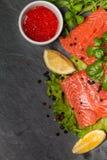 新鲜的三文鱼和红色鱼子酱在黑色的盘子 免版税库存照片