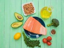 新鲜的三文鱼片断在一棵板材、鲕梨、杏仁、向日葵油和菜的在桌上 库存图片
