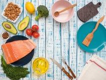 新鲜的三文鱼片断在一棵板材、鲕梨、杏仁、向日葵油和菜的在桌上 免版税图库摄影