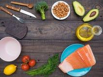 新鲜的三文鱼片断在一棵板材、鲕梨、杏仁、向日葵油和菜的在桌上 库存照片