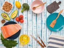新鲜的三文鱼片断在一棵板材、鲕梨、杏仁、向日葵油和菜的在桌上 免版税库存图片