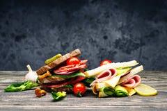 新鲜的三明治用蒜味咸腊肠、菜、火腿和乳酪在一张木桌上 免版税库存图片