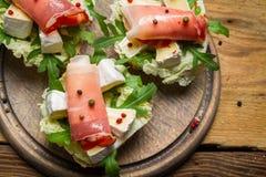 新鲜的三明治用帕尔马火腿、咸味干乳酪乳酪和火箭沙拉 免版税库存照片
