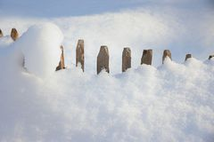 新鲜的下落的粉末雪和被雪包围住的篱芭 免版税库存图片