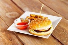 新鲜的乳酪汉堡和土豆油炸物用在白色板材的番茄酱 免版税库存照片