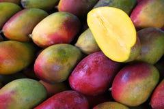 新鲜的五颜六色的芒果在室外水果市场上 库存图片