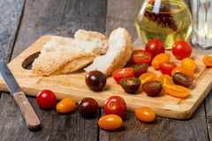 新鲜的五颜六色的蕃茄、橄榄油和面包 库存图片