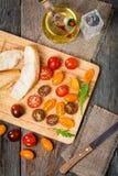 新鲜的五颜六色的蕃茄、橄榄油和面包 免版税库存照片