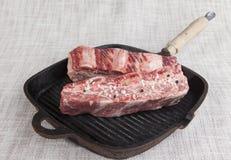 新鲜的使有大理石花纹的牛肉两个片断特写镜头与海盐和黑胡椒的,在铸铁格栅平底锅 库存图片