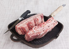 新鲜的使有大理石花纹的牛肉两个片断特写镜头与海盐和黑胡椒,在铸铁格栅平底锅的刀子的 免版税库存照片